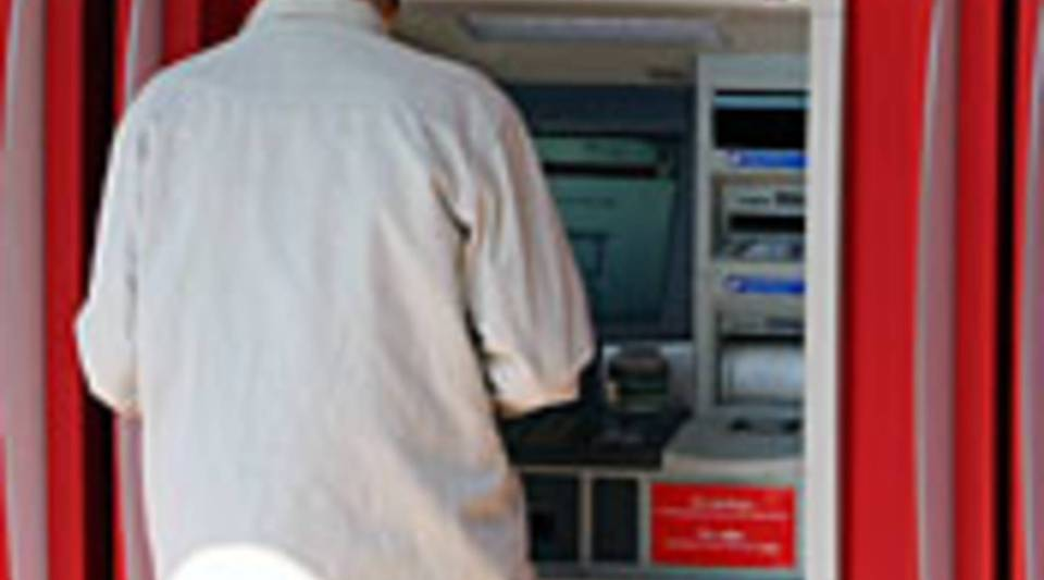 Bank customer uses ATM machine.
