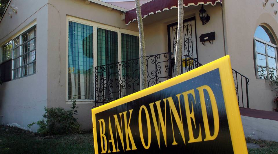A bank owned sign is seen in front of a foreclosed home on December 7, 2010 in Miami, Fla.