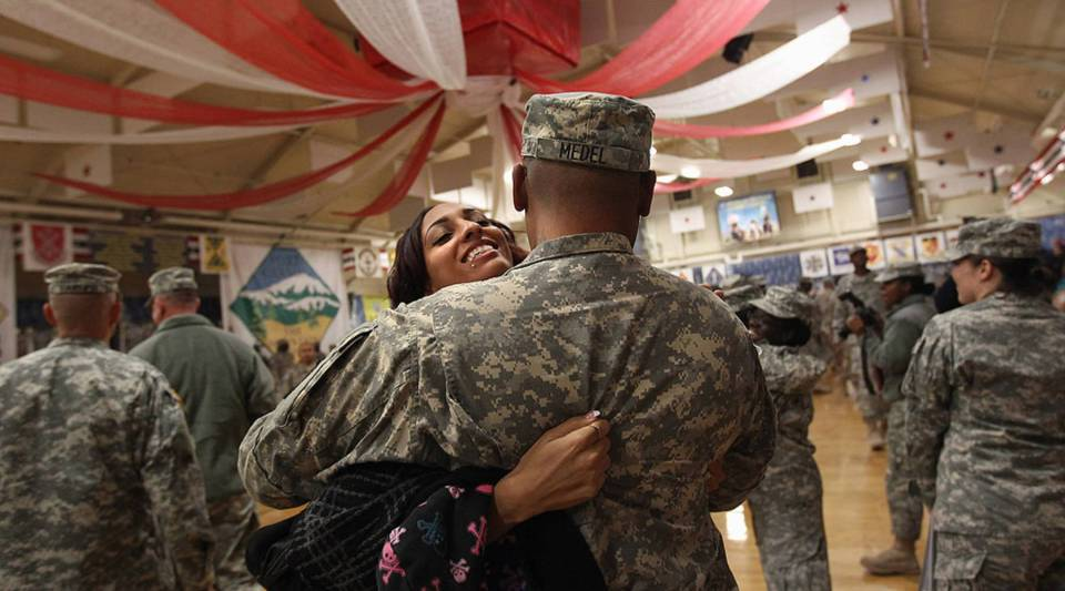 Family members and U.S. soldiers embrace following a welcome home ceremony for troops returning from Iraq.