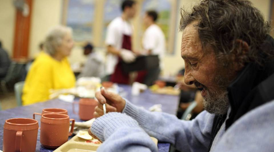 A man named R.J. eats a free meal at the St. Anthony Foundation dining room in San Francisco.