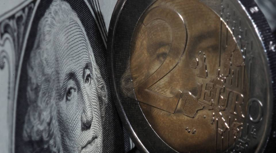 A two Euro coin rest in front of a U.S. dollar. Europe will likely announce a big bond-buying program tomorrow. The U.S. Fed will be watching.