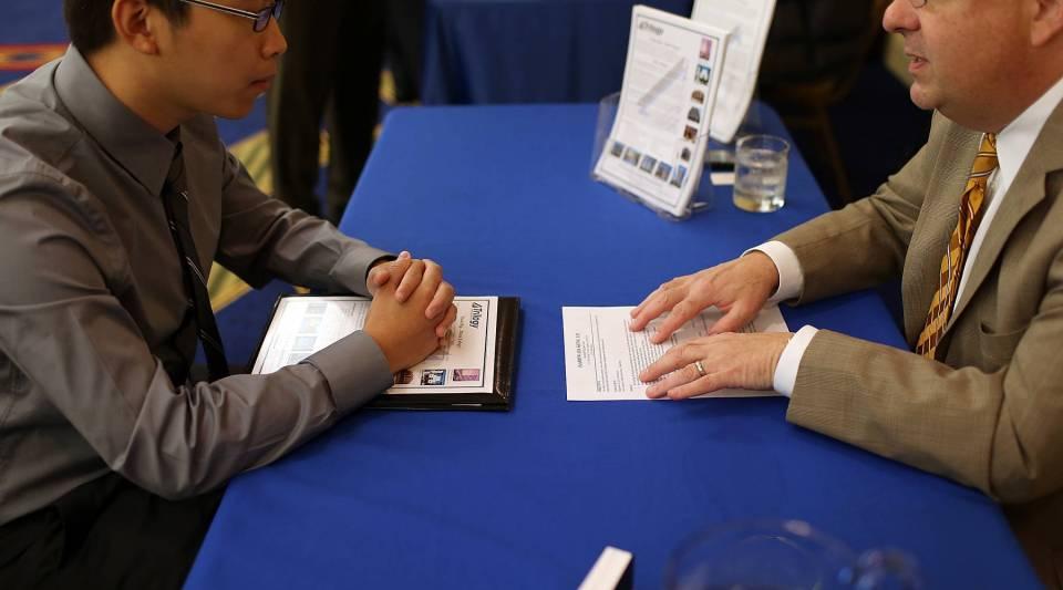 A recruiter (R) talks with a job seeker during the National Career Fairs' San Francisco South Career Fair in San Mateo, Calif.