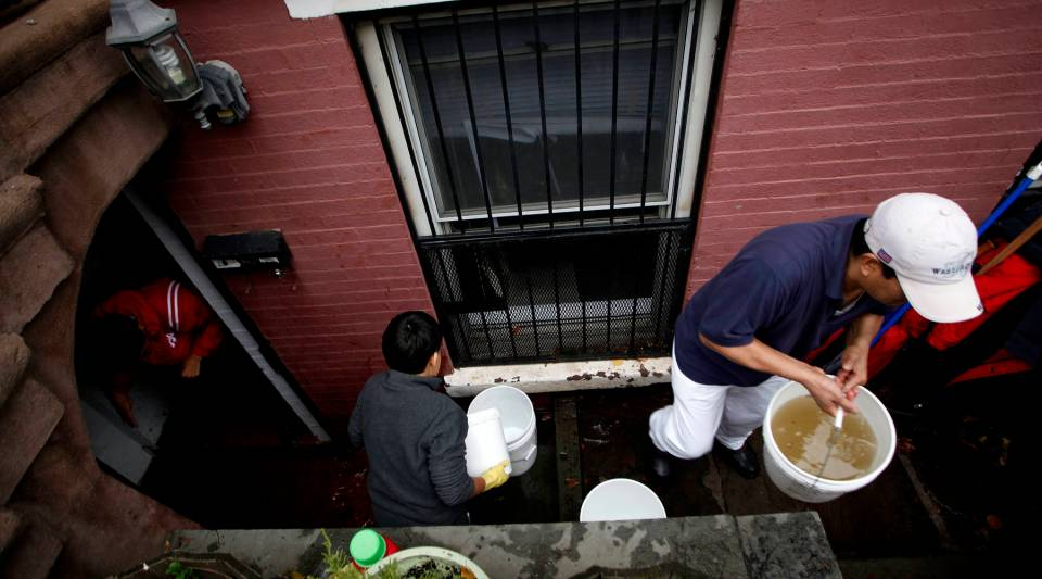 A Hoboken resident clears water from a ground floor apartment on Fifth Street on October 31, 2012 in Hoboken, New Jersey.