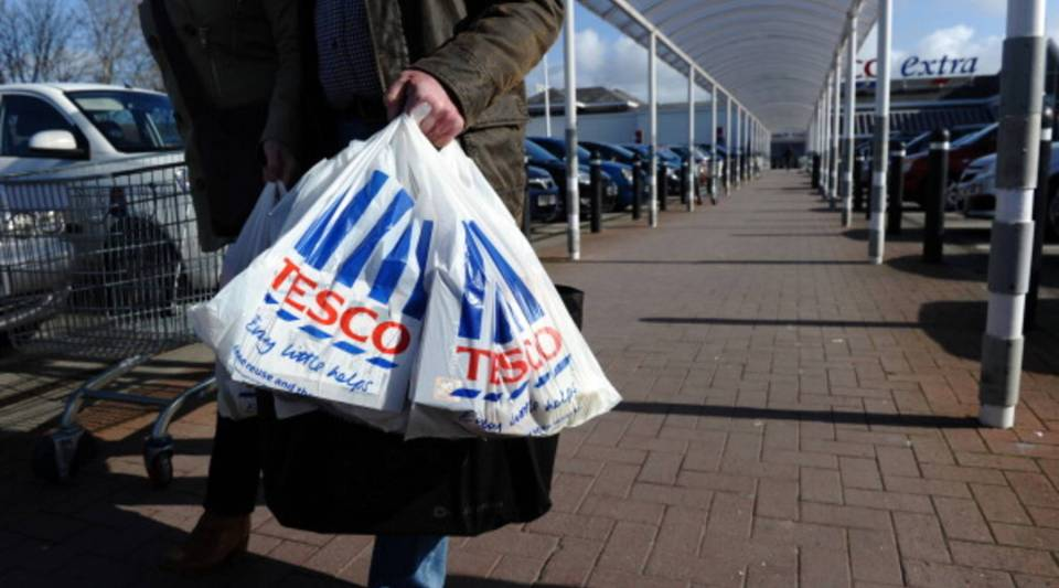 People carry shopping bags through the carpark of a Tesco Extra supermarket in Birkenhead, north-west England.