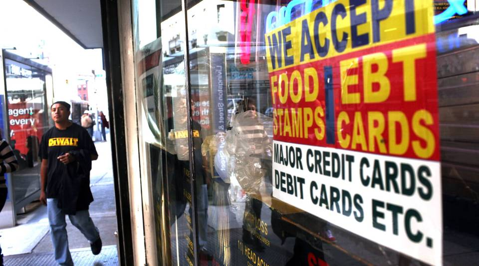 A sign in a market window advertises the acceptance of food stamps in New York City.