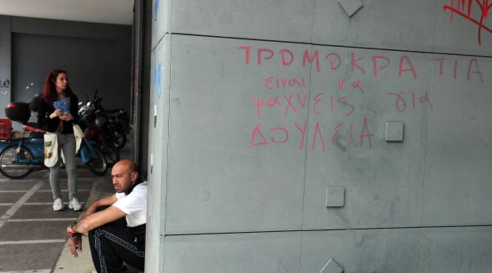 A man sits near the entrance of a Manpower Employment Organization (OAED) office in Athens on May 9, 2013, with graffiti on the wall reading 'terrorism is the search for a job.'