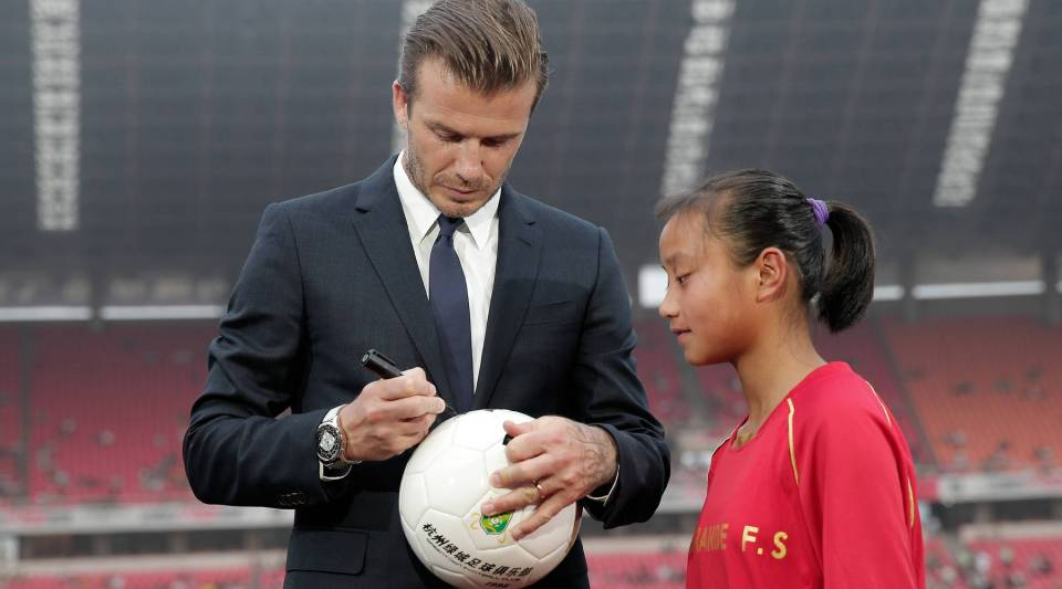 David Beckham signs for young fans during his visit Hangzhou Huanglong Stadium on June 22, 2013 in Hangzhou, China. Now you can get Beckham's signature on Facebook.