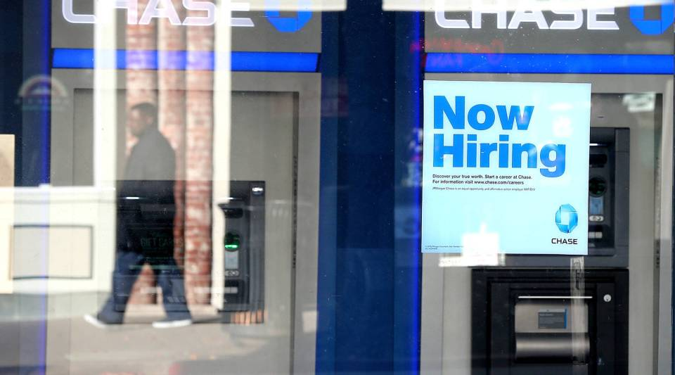A pedestrian walks by a 'now hiring' sign that is posted in the window of a Chase bank branch in San Rafael, California.