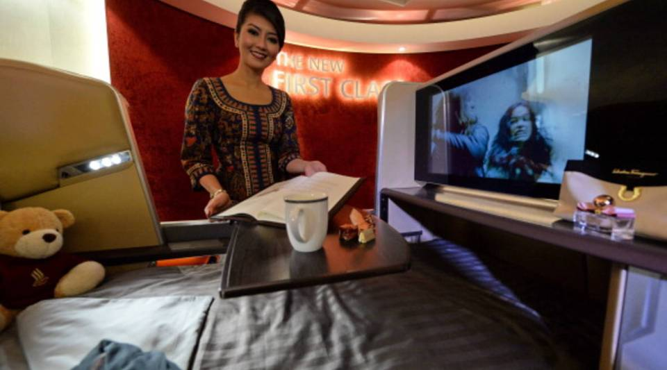 A Singapore Airlines (SIA) stewardess stands next to a display of the new Singapore Airlines First Class seat during their next generation cabin product launch in Singapore.