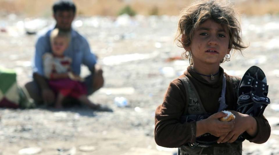 A displaced Iraqi girl from the Yazidi community holds a piece of bread after crossing the Iraqi-Syrian border at the Fishkhabur crossing, in northern Iraq, on August 11, 2014. Most of the Yazidi is out of reach for humanitarian aid workers.