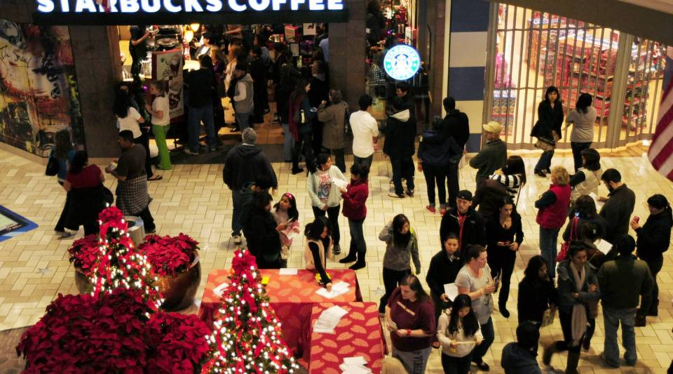 Shoppers wait in line at Starbucks while shopping at a Black Friday event.