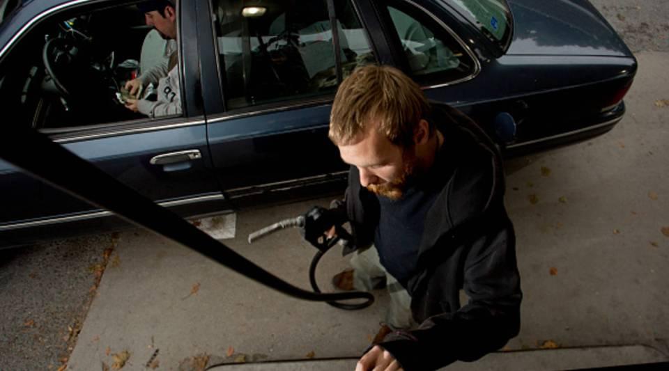 A man prepares to pump gas as a customer counts his money.