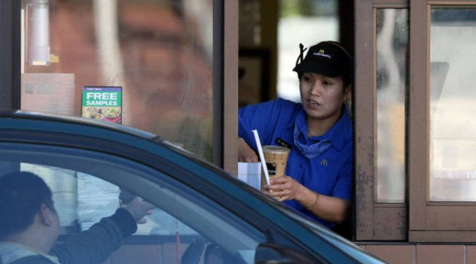 A McDonald's drive-through worker hands an order to a customer in San Francisco.