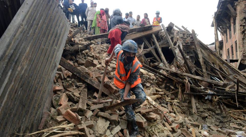 Nepalese rescue personnel and volunteers observe damaged buildings in Bhaktapur, Nepal, two days after a 7.8 magnitude earthquake hit the country.