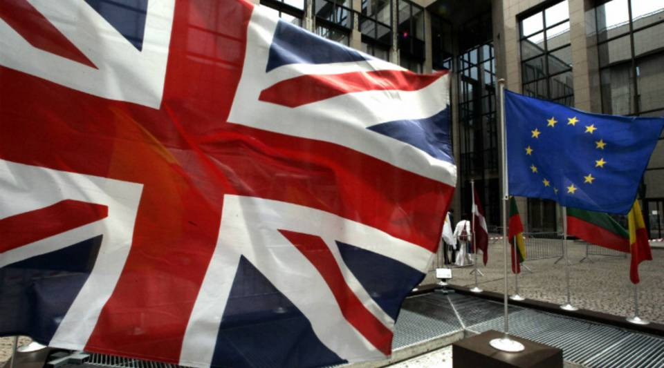 Some in the U.K. want Britain to exit the European Union, whose flag, right, flies next to the Union Jack at EU headquarters in Brussels. Those Britons are angry about the EU's treatment of Greece.