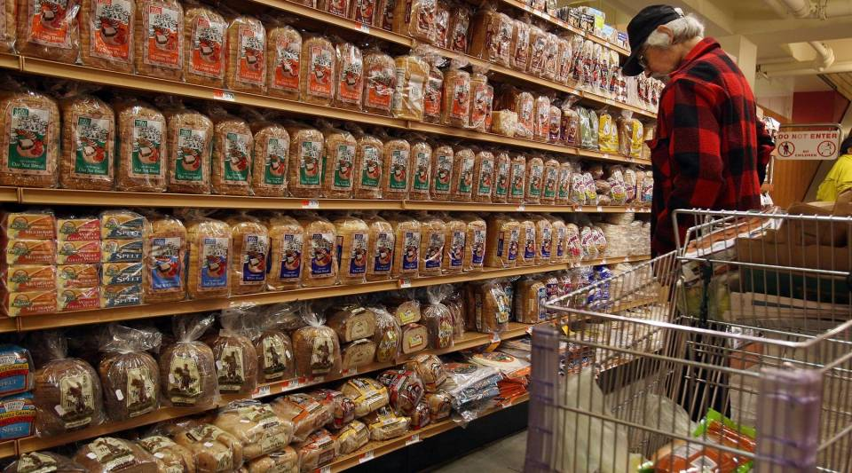A man in the bread aisle of a supermarket.