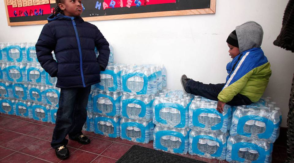 Justin Roberson, age 6, and Mychal Adams, age 1, wait on a stack of bottled water at the Heavenly Host Baptist Church January 17, 2016 in Flint, Michigan.