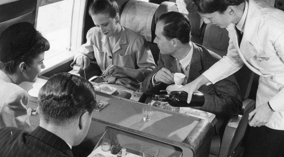 A stewardess serving drinks whilst passengers have lunch aboard a BEA Vickers Viking passenger plane, 1958.