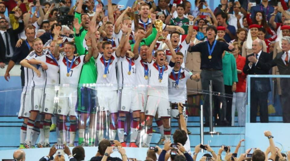 Philipp Lahm of Germany lifts the World Cup trophy with teammates after defeating Argentina 1-0 in extra time as FIFA President Joseph S. Blatter and German Chancellor Angela Merkel look on during the 2014 FIFA World Cup Brazil Final match between Germany and Argentina at Maracana on July 13, 2014 in Rio de Janeiro, Brazil.