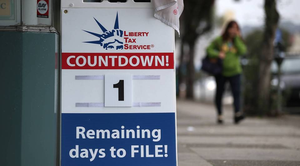: A sign advertising one day remaining before the tax filing deadline is posted in front of a Liberty Tax Service.