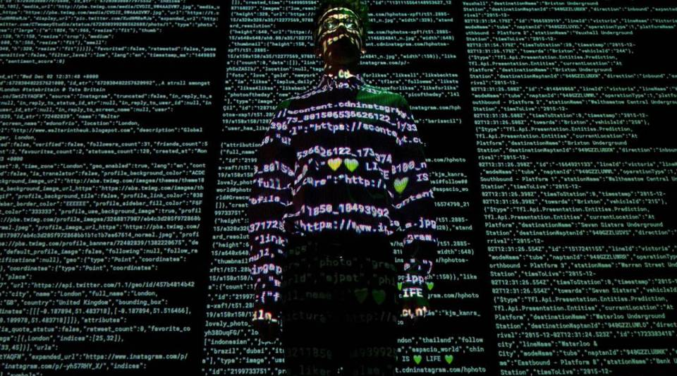"""A staff member at theSomerset House in London stands in front of an art exhibit themed on big data. Rick Smolan, executive producer of the film """"The Human Face of Big Data,"""" says our relationship to data isn't black and white."""