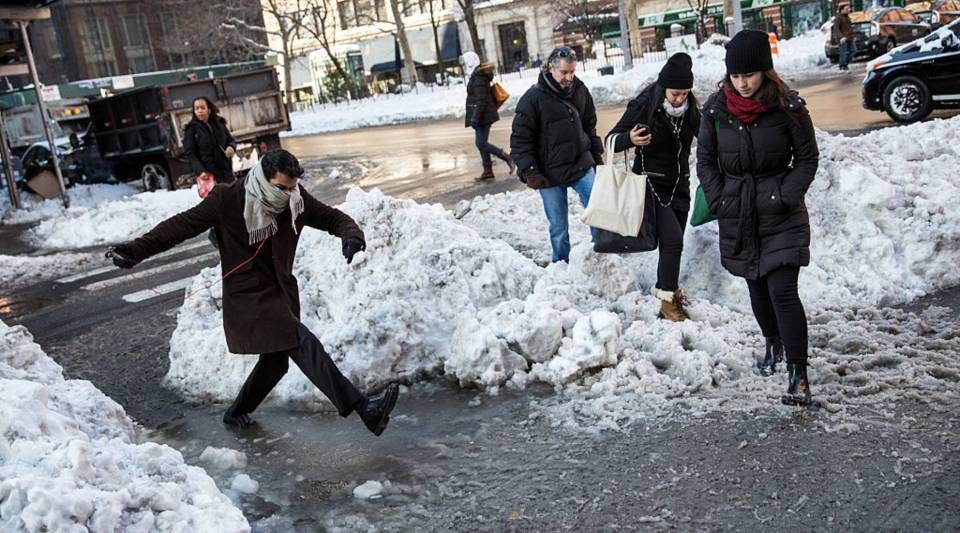 A man jumps over a snow and puddle filled street two days after a massive snow storm covered the East Coast in snow on January 25, 2016 in New York City.