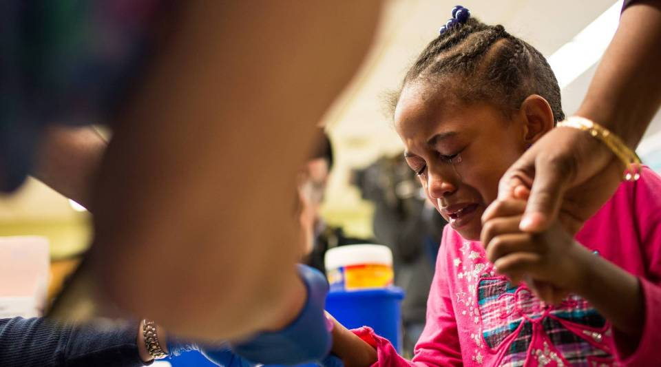 Tears stream down the face of Morgan Walker, age 5 of Flint, as she gets her finger pricked for a lead screening on January 26, 2016 at Eisenhower Elementary School in Flint Michigan.