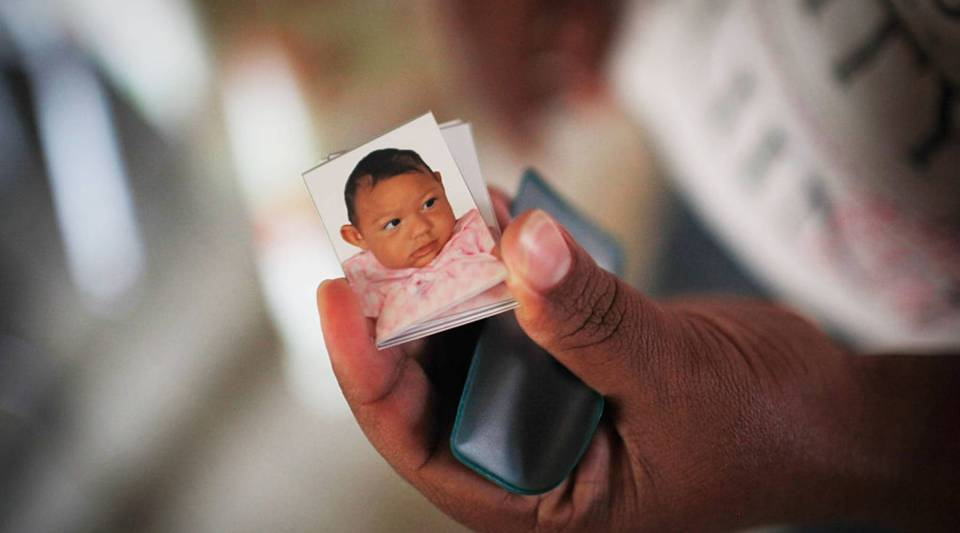 Mother Nadja Cristina Gomes Bezerra displays a photograph she had taken for identification of her daughter Alice Vitoria Gomes Bezerra, 3-months-old, who has microcephaly, on January 31, 2016 in Recife, Brazil. In the last four months, authorities have recorded close to 4,000 cases in Brazil in which the mosquito-borne Zika virus may have led to microcephaly in infants.