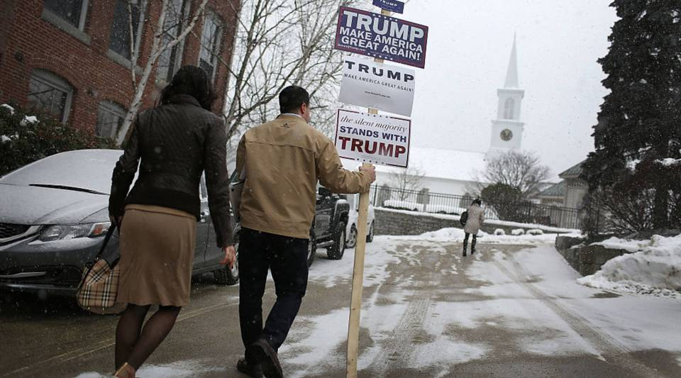 A volunteer carries a campaign sign supporting Republican presidential candiate Donald Trump as he leaves the Newmarket Trump campaign headquarters on February 8, 2016 in New Hampshire.