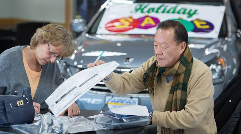 A woman signs a contract with a sales consultant at a Hyundai dealership.