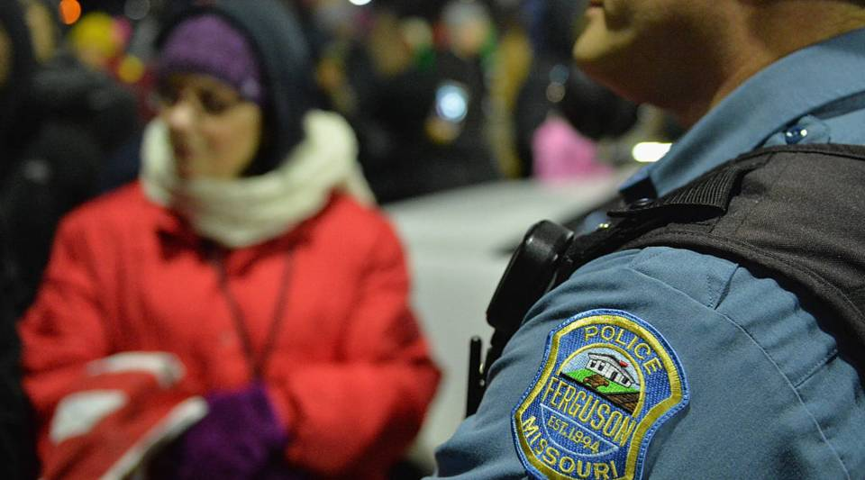 A Ferguson police officer listens to the concerns of a protester as they demonstrate outside the Ferguson Police Department in Ferguson, Missouri on March 4, 2015.