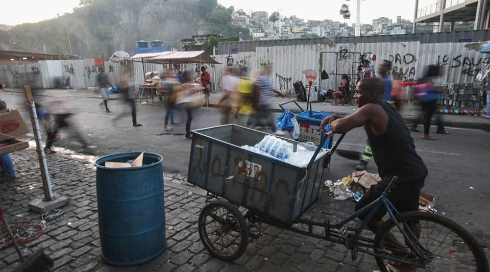 A vendor stands in front of the new gondola which travels to the top of the Providencia community, or favela, on September 23, 2015 in Rio de Janeiro, Brazil.