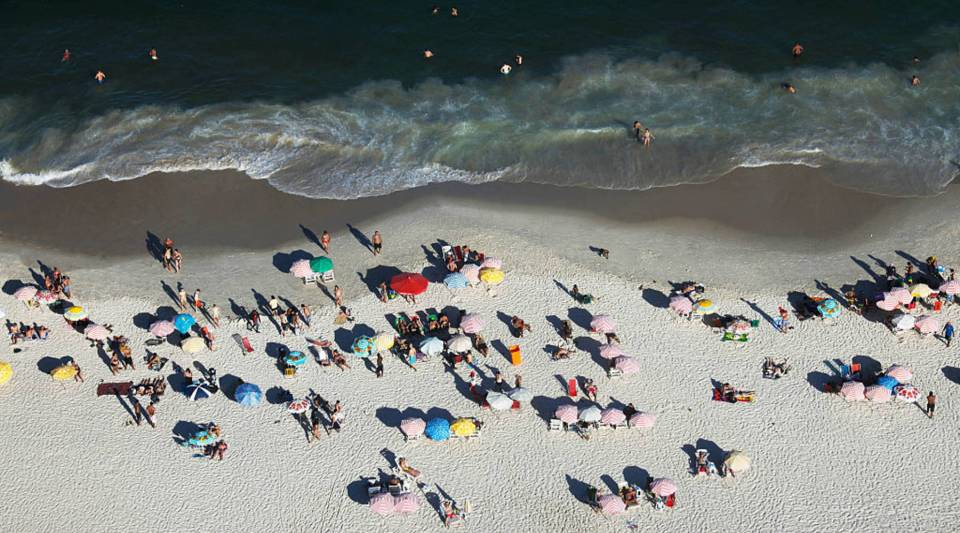People gather on Copacabana beach, a landmark tourist destination in Rio, on February 26, 2016 in Rio de Janeiro, Brazil. The Zika virus outbreak, which may be linked to a surge in microcephaly cases in the country, is threatening tourism in Brazil which expects to profit from hundreds of thousands of foreign visitors travelling to Rio de Janeiro during the Rio 2016 Olympic Games. The World Health Organization (WHO) has declared the outbreak, centered in Brazil, to be a 'public health emergency of international concern'.