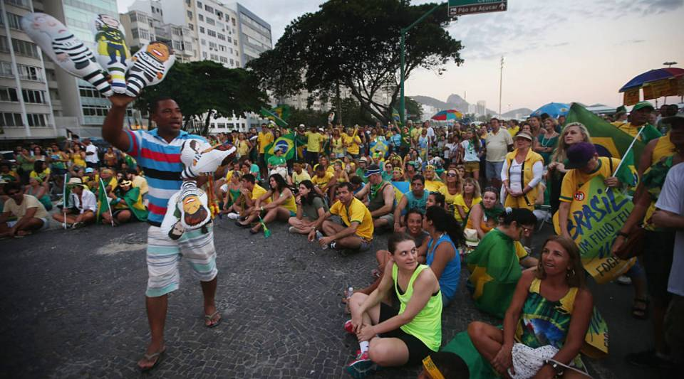 RIO DE JANEIRO, BRAZIL - APRIL 17: Pro-impeachment supporters watch a live television broadcast as a vendor sells political balloons while lower house deputies prepare to cast their votes in the impeachment process of President Dilma Rousseff on April 17, 2016 in Rio de Janeiro, Brazil. President Rousseff is facing a crucial impeachment vote in the lower house of Congress today. Rio will host the Rio 2016 Olympic Games in August.