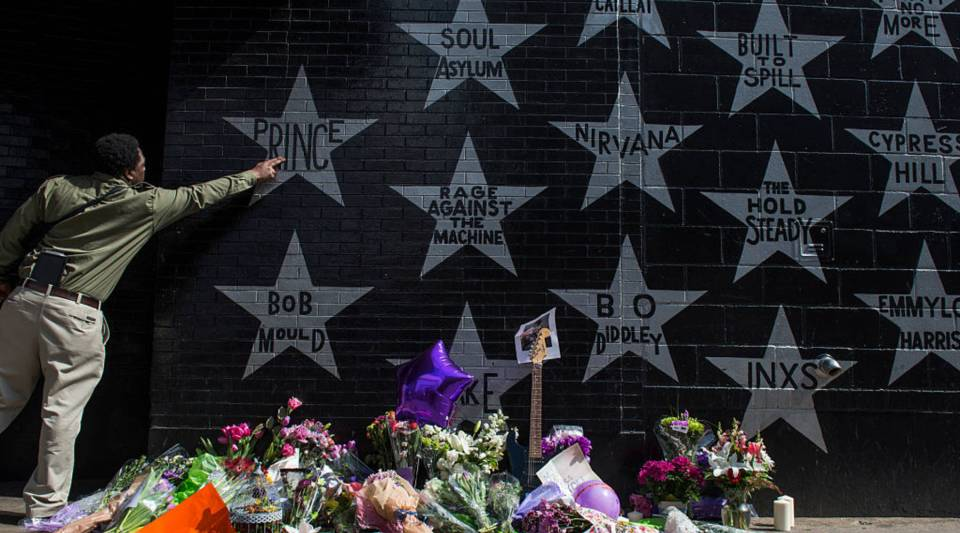 A man touches the Prince star on the wall outside the First Avenue nightclub Thursday in Minneapoli. Prince died earlier today at his Paisley Park compound at the age of 57.