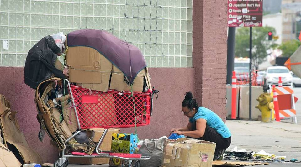 A homeless woman packs up her belongings after a night sleeping on the street in Los Angeles.