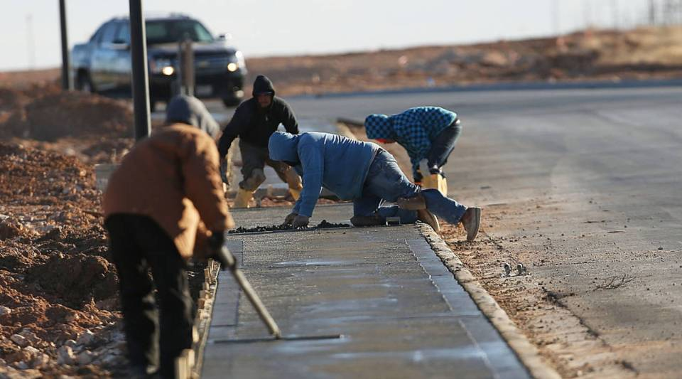 Workers construct new sidewalks in the Permian Basin oil field on January 21, 2016 in the oil town of Midland, Texas.