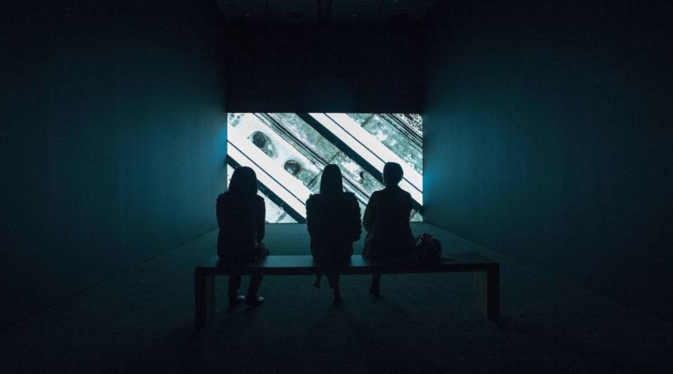"""People watch an art piece entitled """"Shadow Sites II"""" by Jananne Al-Ani, inside the San Francisco Museum of Modern Art in San Francisco, California on April 28, 2016. The newly redesigned museum integrates a 10-story expansion in a new building and will open to the public on May 14, 2016."""