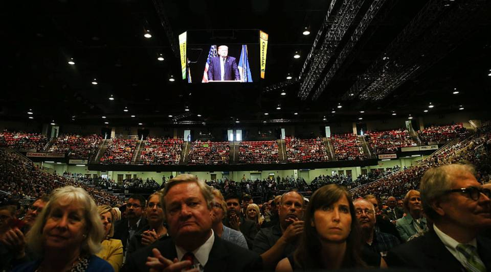 People watch as Republican presidential candidate Donald Trump speaks at a rally on May 26, 2016 in Bismarck, North Dakota.