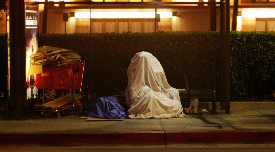 A homeless person covers up on a bus stop bench before dawn October 12, 2007 in downtown Los Angeles, California.