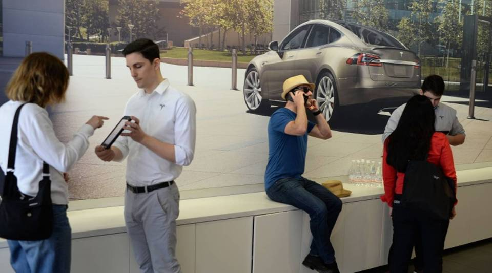 A salesman helps a customer pre-order the as-yet-unseen Tesla Model 3 in the Tesla store in Santa Monica, California, on March 31.