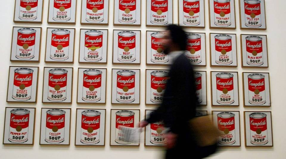"""A spectator walks past Andy Warhol's """"Campbells Soup Cans"""" at the 2002 Warhol retrospective exhibition at the Tate Modern Gallery in London."""