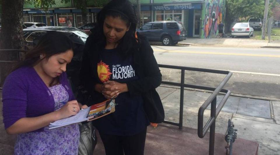 "Wanda Gomez registers voters outside a grocery store during her sons' spring break. Her sons say ""Today is a pool day,"" but Gomez has to work."