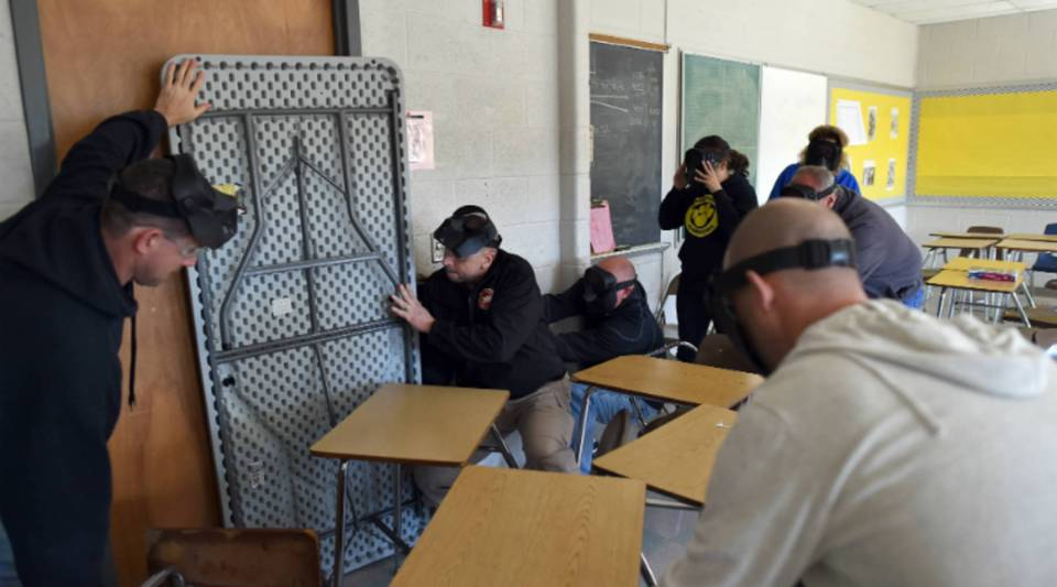 """An """"active shooter"""" enters a classroom as """"students"""" take cover during ALICE training at Harry S. Truman High School in Levittown, Pennsylvania, in 2015."""
