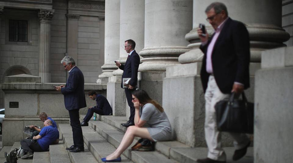 City workers talk on their mobile phones near the Bank of England as the financial markets face uncertainty in the wake of Brexit on June 27, 2016 in London, England.