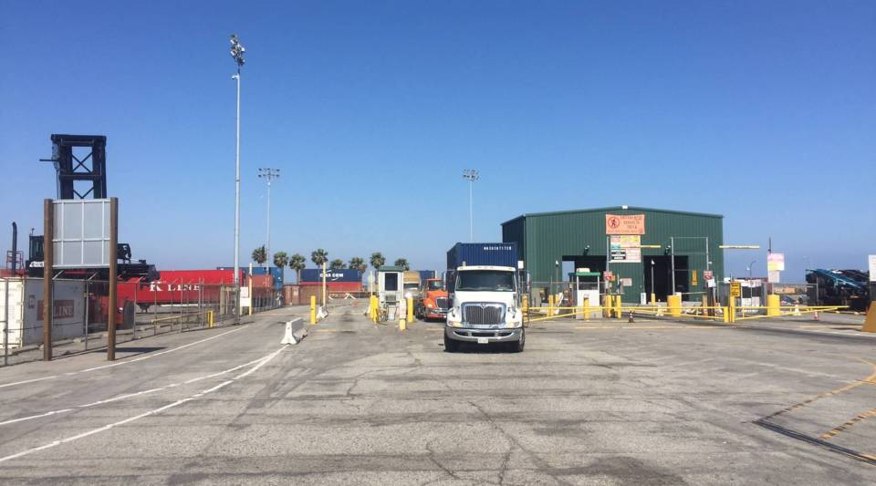 A truck pulls out of the port of Los Angeles carrying a container.