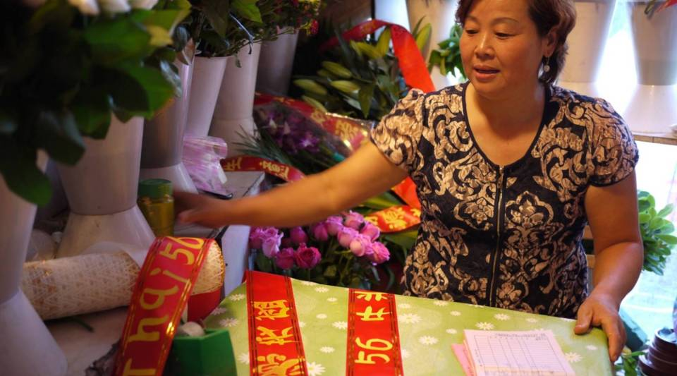 Zhao Shiling arranges flowers in her tiny shop along the Street of Eternal Happiness in Shanghai. 25 years ago, she left her village to work at a factory in Shanghai, and now she runs her own shop, earning money for her sons. Her abusive husband, though, has lost his job and has recently come to Shanghai.