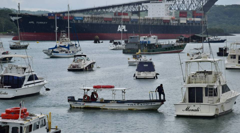 A container ship exits the Panama Canal toward the Pacific Ocean, with the Balboa Yacht Club in the fore.
