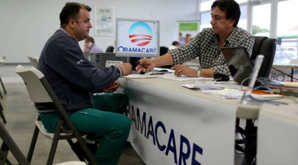 Ariel Fernandez (L) sits with Noel Nogues, an insurance advisor with UniVista Insurance company, as he signs up for the Affordable Care Act.