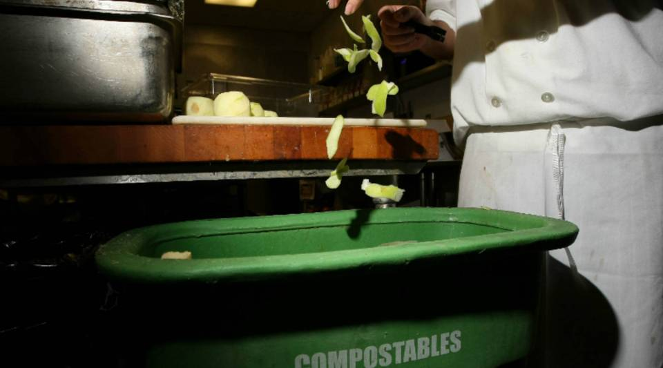 A prep cook at a San Francisco restaurant drops apple skins into a food scrap recycling container.